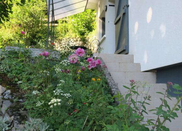 La montée d'escaliers vers la porte d'entrée et la terrasse couverte